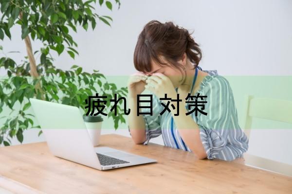 目頭を押さえる女性とノートパソコン